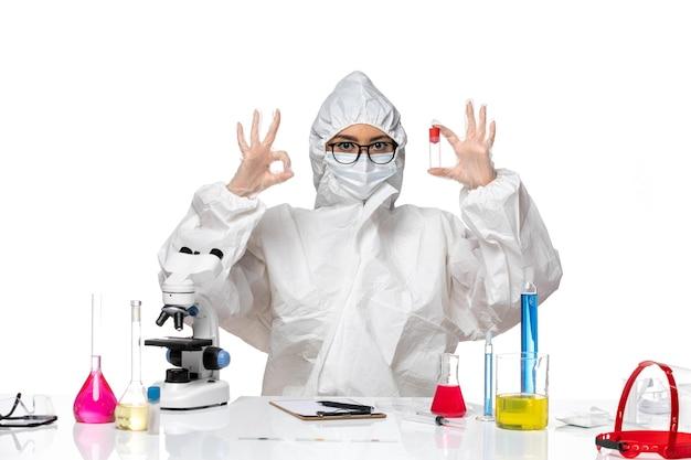 밝은 흰색 배경 바이러스 건강 화학 covid-에 플라스크를 들고 특수 보호 복에 전면보기 여성 화학자
