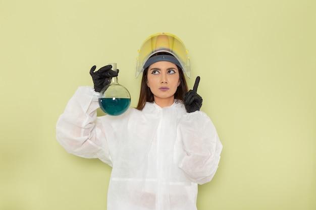 파란색 솔루션 플라스크를 들고 녹색 표면에 생각하는 특수 보호 복의 전면보기 여성 화학자
