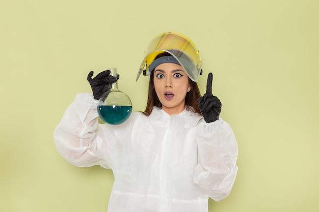 녹색 표면에 파란색 솔루션으로 플라스크를 들고 특수 보호 복에 전면보기 여성 화학자
