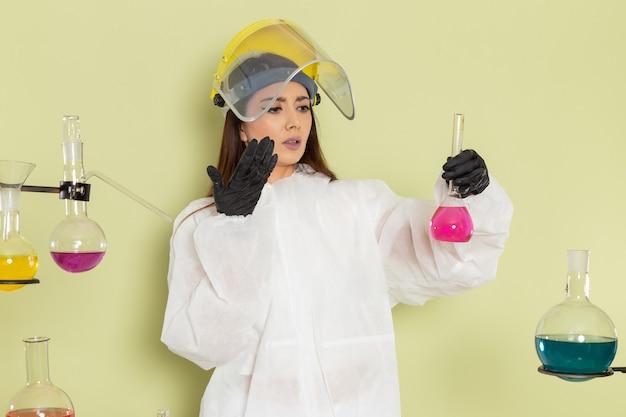 녹색 표면에 분홍색 솔루션으로 플라스크를 들고 특수 보호 복에 전면보기 여성 화학자