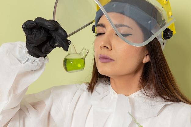 녹색 표면에 녹색 솔루션을 들고 특수 보호 복에 전면보기 여성 화학자