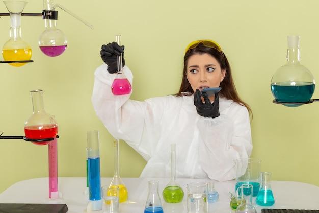 薄緑色の表面にピンクの溶液を保持している特別な防護服の正面図の女性化学者