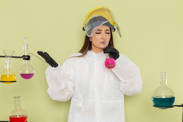 Женщина-химик, вид спереди в специальном защитном костюме, держит розовый раствор, нюхает его на зеленой поверхности