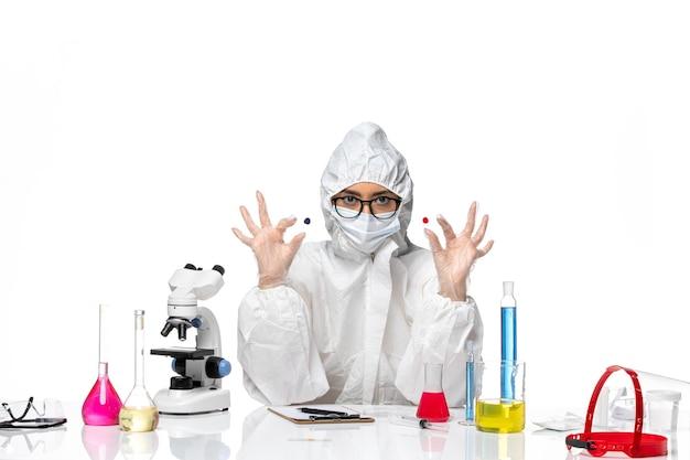 흰색 배경 바이러스 화학 covid 유행성 건강에 샘플을 들고 특수 보호 복에 전면보기 여성 화학자