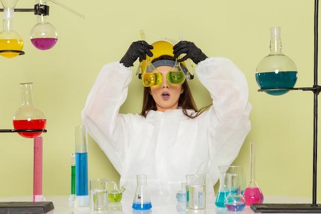 緑の表面にソリューションを保持している特別な防護服の正面図の女性化学者
