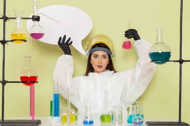 緑の表面に白い看板とソリューションを保持している特別な防護服の正面図の女性化学者