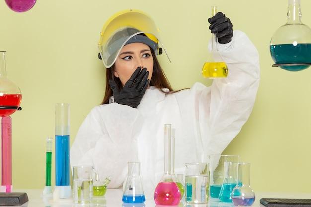 緑の表面に黄色の溶液を保持している特別な防護服の正面図の女性化学者
