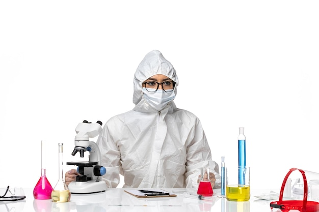 白い背景の化学covid-健康ウイルスに座っているだけで特別な防護服を着た正面図の女性化学者