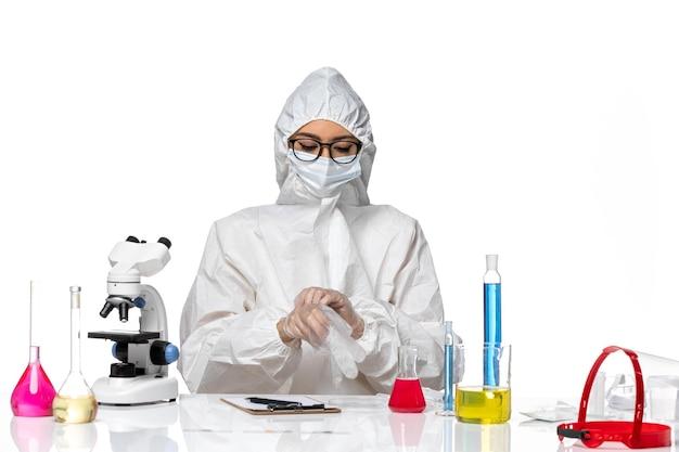 흰색 배경 화학 유행성 코로나 바이러스에 대한 솔루션과 함께 앉아 특수 보호 복에 전면보기 여성 화학자