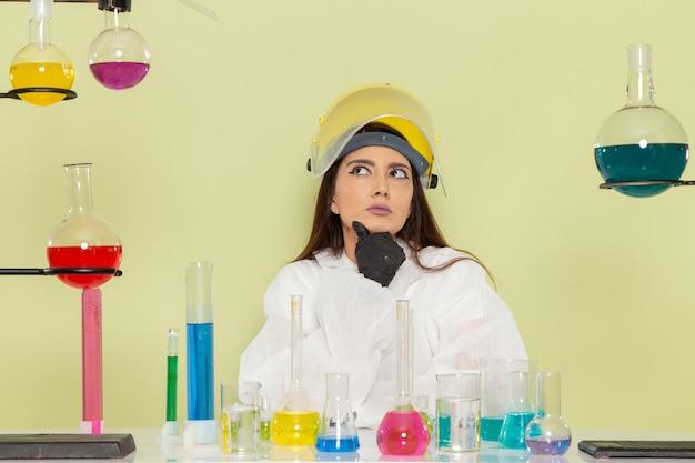 薄緑色の表面を考えて特別な防護服を着た女性化学者の正面図
