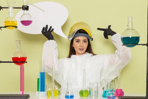 緑の表面に白い看板を保持しているさまざまなソリューションで作業している特別な防護服の正面図の女性化学者