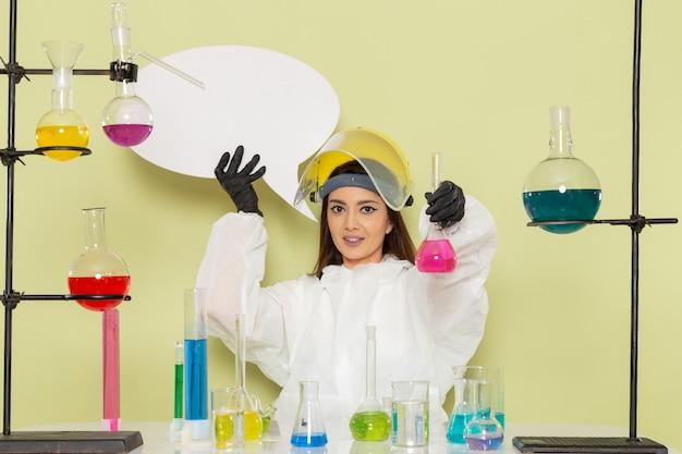 緑の表面でさまざまなソリューションを使用して作業している特別な防護服の正面図の女性化学者