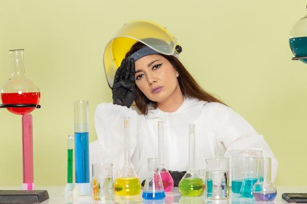 特別な防護服を着た女性化学者の正面図ソリューションで作業し、緑の表面に疲れを感じています