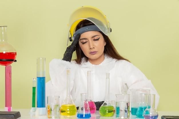 解決策を扱い、緑の表面に頭痛がある特別な防護服を着た女性化学者の正面図