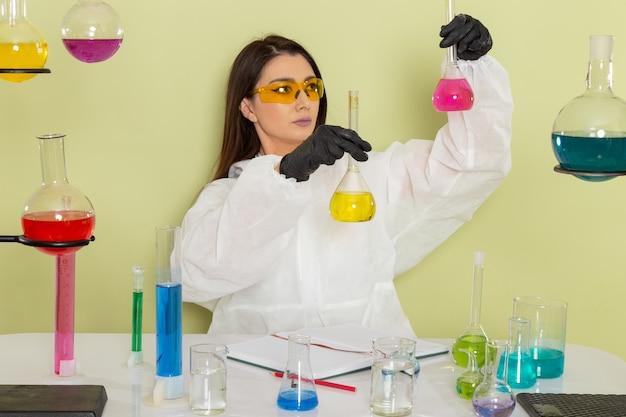 緑の表面のソリューションで作業している特別な防護服の正面図の女性化学者