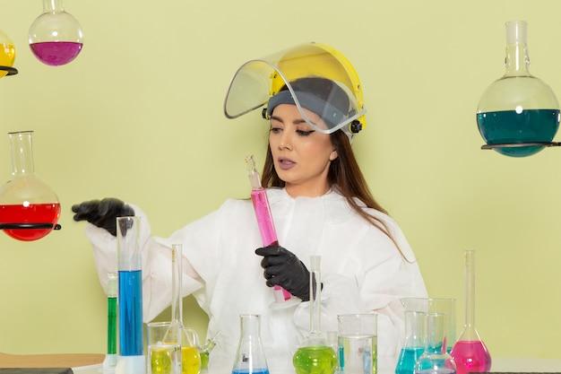 Вид спереди женщина-химик в специальном защитном костюме, работающая с растворами на светло-зеленом столе