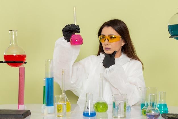 Вид спереди женщина-химик в специальном защитном костюме, работающая с решениями, думая на зеленом столе