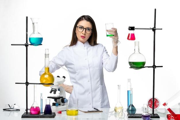 흰색 배경에 솔루션으로 플라스크를 들고 멸균 의료 소송에서 전면보기 여성 화학자 실험실 바이러스 covid- 유행성 과학