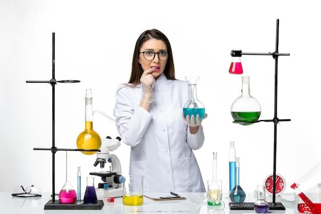 흰색 배경 바이러스 covid- 대유행 과학에 솔루션으로 플라스크를 들고 멸균 의료 소송에서 전면보기 여성 화학자