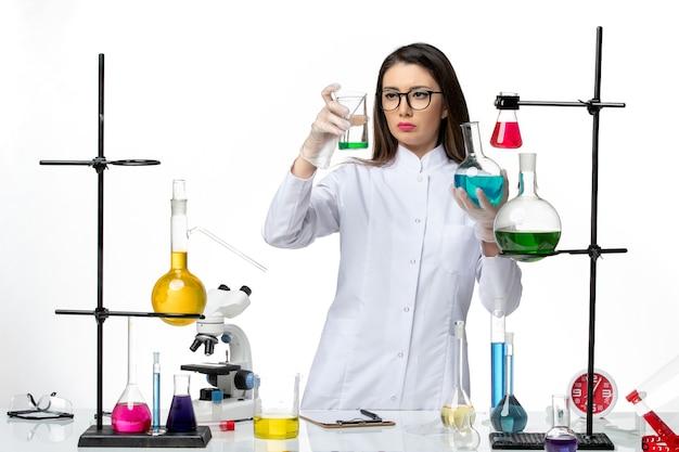 Вид спереди женщина-химик в стерильном медицинском костюме, держащая колбы с растворами на белом фоне, вирус covid - пандемическая наука