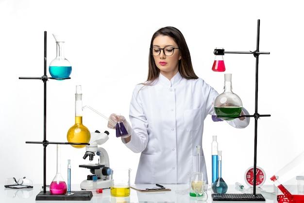 밝은 흰색 배경 바이러스 질병 Covid- Pandemic 과학에 솔루션으로 테이블 주위에 서있는 멸균 의료 소송에서 전면보기 여성 화학자 무료 사진