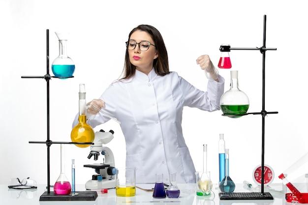 흰색 배경 바이러스 질병 covid 실험실 유행 과학에 솔루션 테이블 주위에 서있는 멸균 의료 소송에서 전면보기 여성 화학자