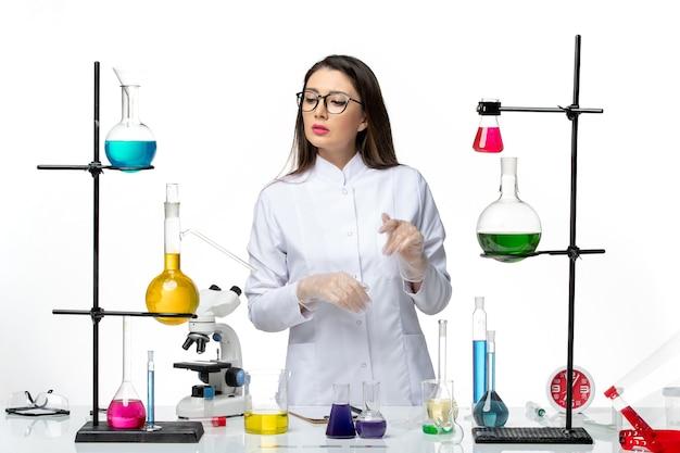 Вид спереди женщина-химик в стерильном медицинском костюме, стоящая вокруг стола с растворами на белом столе, вирусная болезнь, covid- lab, пандемия науки