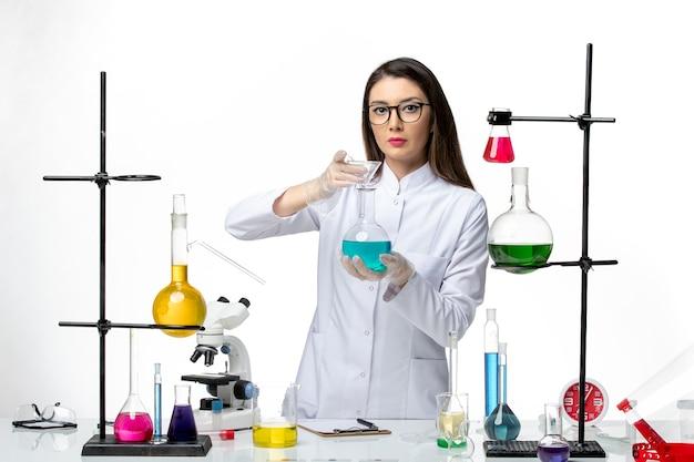 흰색 배경 바이러스 covid- 유행성 과학에 다른 솔루션으로 작업하는 멸균 의료 소송에서 전면보기 여성 화학자