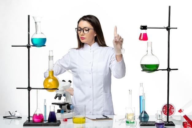 흰색 배경 바이러스 covid- 실험실 유행성 과학에 다른 솔루션으로 작업하는 멸균 의료 소송에서 전면보기 여성 화학자
