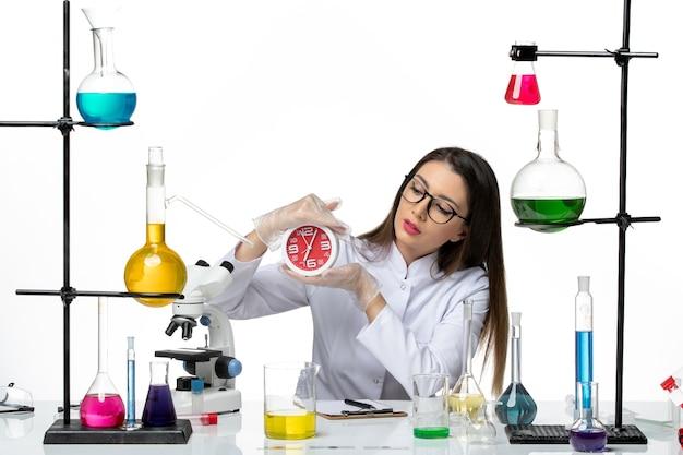 明るい白の背景に時計を保持している白い医療スーツの正面図女性化学者科学ウイルス研究所のパンデミック