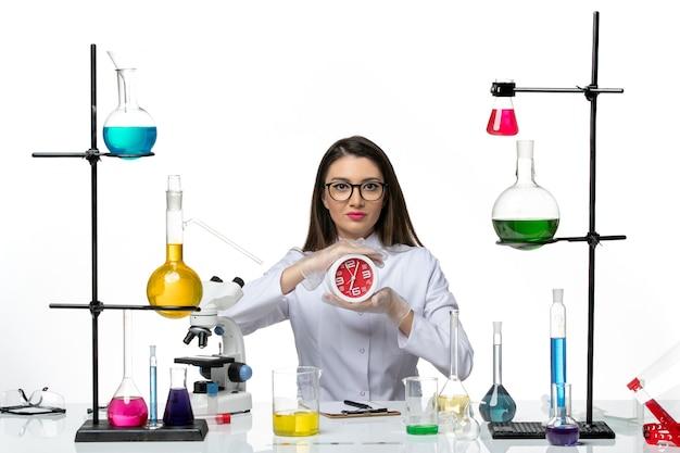 白い床の科学ウイルス研究所のパンデミックで時計を保持している白い医療スーツの正面図の女性化学者