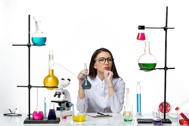 밝은 흰색 배경에 파란색 솔루션으로 플라스크를 들고 흰색 의료 소송에서 전면보기 여성 화학자 실험실 과학 바이러스 covid 전염병