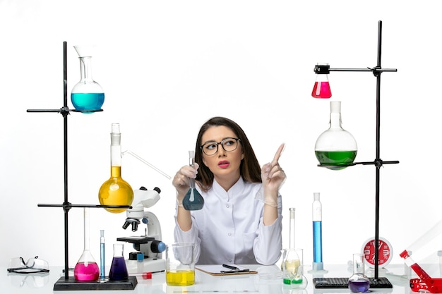 白い机の上の青い解決策とフラスコを保持している白い医療スーツの正面図女性化学者ラボ科学ウイルスcovidパンデミック