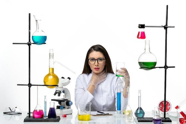 白い背景の科学ウイルス共同パンデミックラボで溶液とフラスコを保持している白い医療スーツの正面図女性化学者