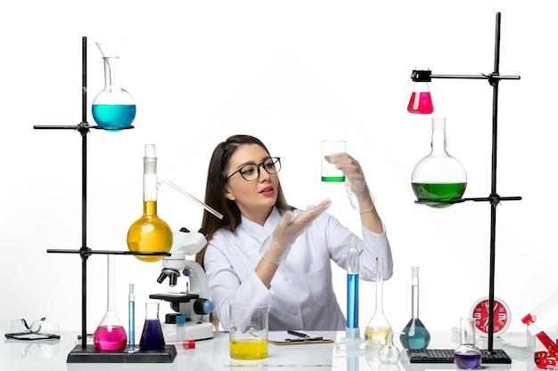 白い背景の実験室科学ウイルスcovidパンデミックのソリューションとフラスコを保持している白い医療スーツの正面図女性化学者