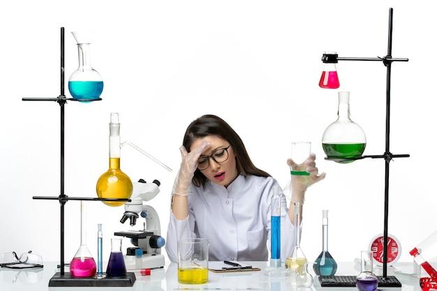 솔루션 흰색 배경 과학 바이러스 covid- 대유행 실험실과 플라스크를 들고 흰색 의료 소송에서 전면보기 여성 화학자