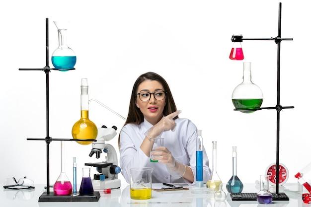 白い机の上のソリューションとフラスコを保持している白い医療スーツの正面図女性化学者科学ウイルスcovidパンデミックラボ