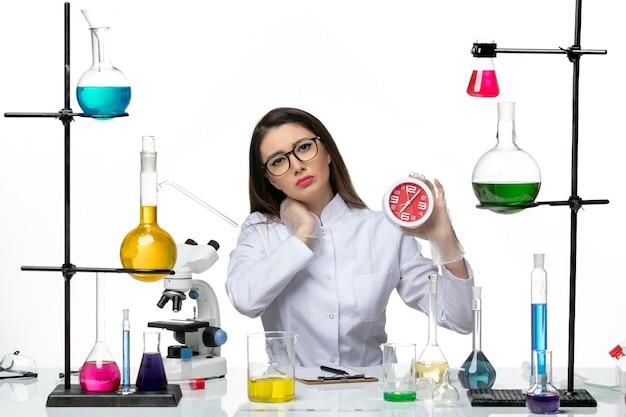 밝은 흰색 배경에 빨간 시계를 들고 흰색 의료 소송에서 전면보기 여성 화학자 과학 바이러스 covid- pandemic lab