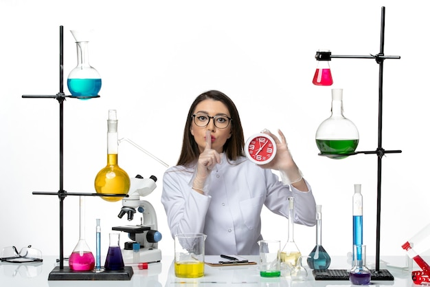白い背景の科学ウイルス研究所のパンデミックに赤い時計を保持している白い医療スーツの正面図女性化学者