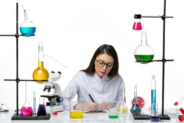 ちょうど解決策と座って、白い背景の科学パンデミックラボウイルスcovidにメモを書いている白い医療スーツの正面図の女性化学者
