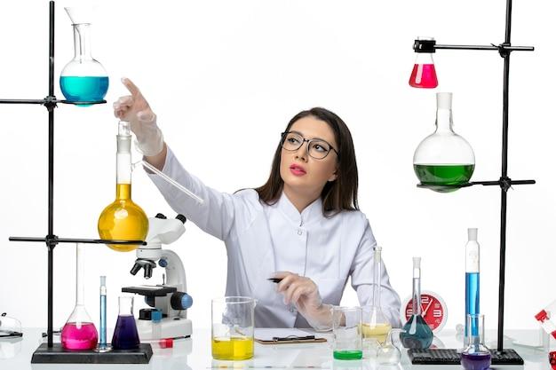 흰색 배경 Covid- 과학 전염병 실험실 바이러스에 솔루션과 함께 앉아 흰색 의료 소송에서 전면보기 여성 화학자 무료 사진