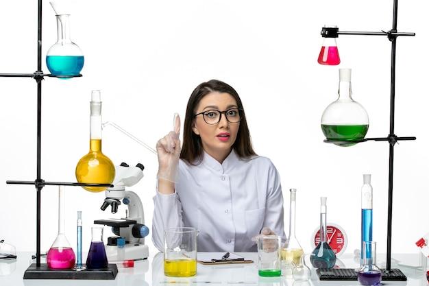 明るい白の背景科学パンデミックラボウイルスcovidのソリューションとちょうど座っている白い医療スーツの正面図の女性化学者