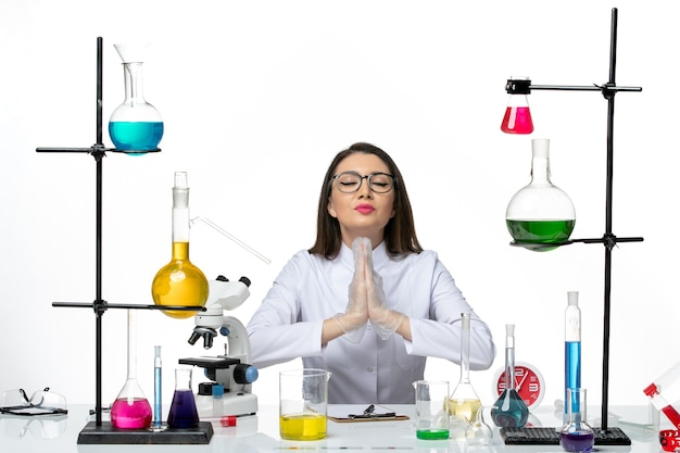 白い背景の科学covid-labパンデミックウイルスのソリューションと一緒に座っている白い医療スーツの正面図の女性化学者