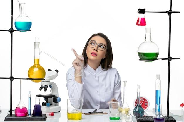 白い背景の科学パンデミックラボウイルスcovidのソリューションと一緒に座っている白い医療スーツの正面図の女性化学者