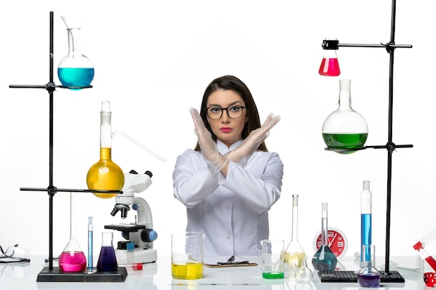 白い医療スーツを着た女性化学者の正面図白い背景の科学covidパンデミックラボウイルスの禁止サインを示すソリューションと一緒に座っている