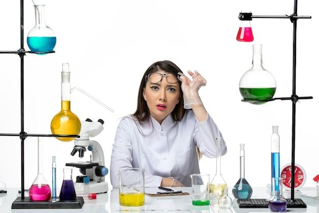 Вид спереди женщина-химик в белом медицинском костюме смотрит с вниманием на белом фоне научный вирус covid- пандемическая лаборатория