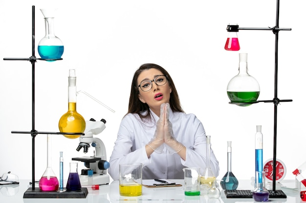 白い背景の科学ウイルスの共同パンデミックラボで祈っている白い医療スーツの正面図の女性化学者