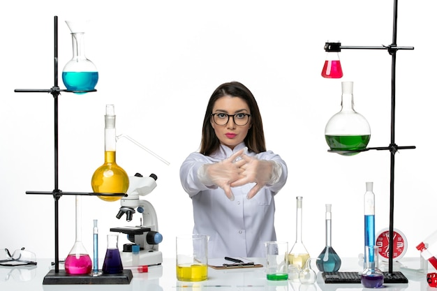 白い背景の科学ウイルスの共同パンデミックラボでの作業の準備をしている白い医療スーツの正面図の女性化学者