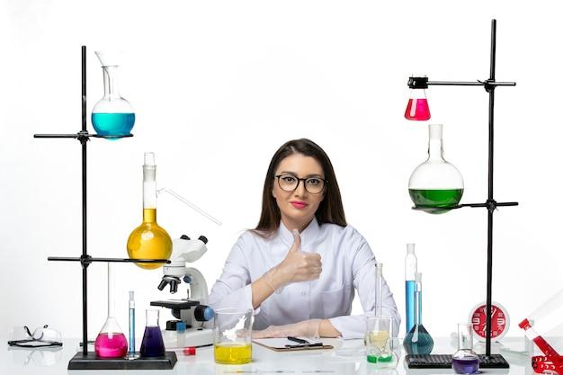 白い背景に座って笑っている白い医療スーツの正面図女性化学者ラボウイルスcovidパンデミック科学