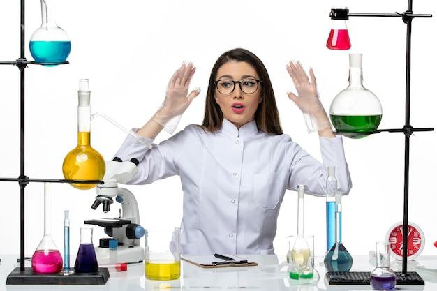 흰색 책상에 앉아 흰색 의료 소송에서 전면보기 여성 화학자 실험실 과학 바이러스 코로나 바이러스 전염병